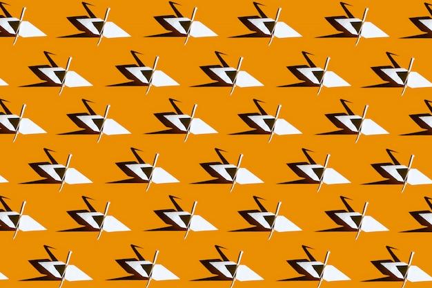 Papier origami kranen collage op een fel gele achtergrond met harde schaduw