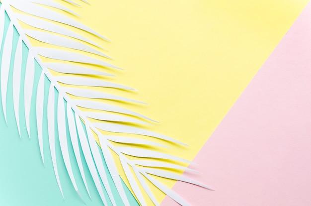 Papier palmblad op veelkleurige tafel