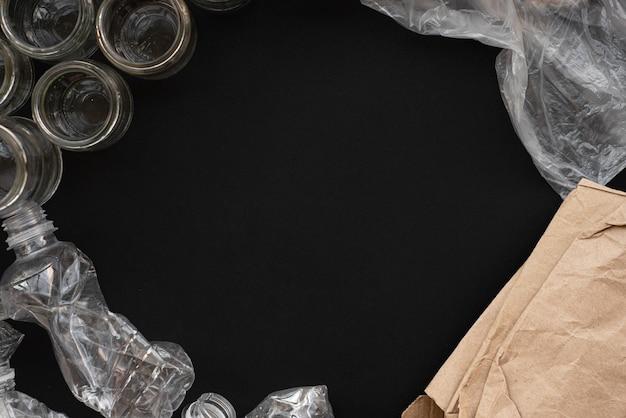 Papier, plastic en glasafval en vuilnis op zwarte achtergrond. recycling. kopieer ruimte.