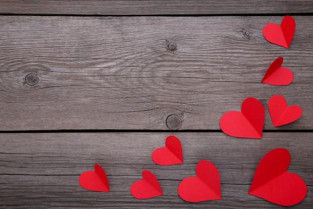 Papier rode harten op een grijze achtergrond.