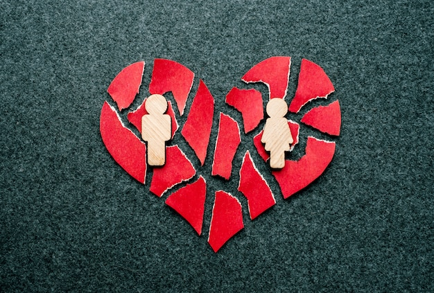 Papier rood gebroken hart met houten figuren van man en vrouw