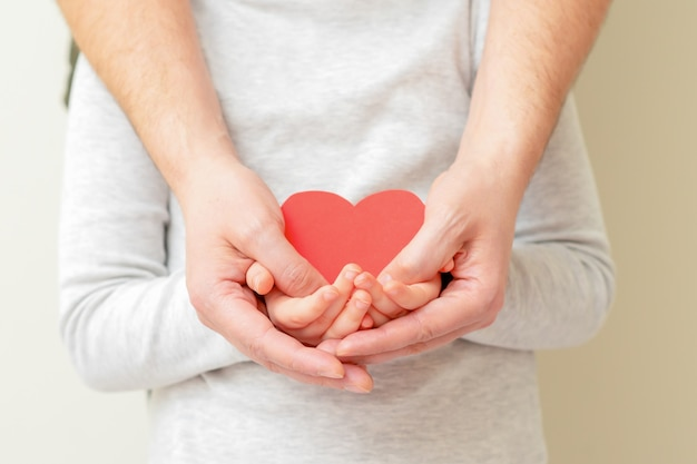 Papier rood hart in handen van mannelijke vader en klein kind meisje op gele achtergrond thuis. concept van een gezond gezin.