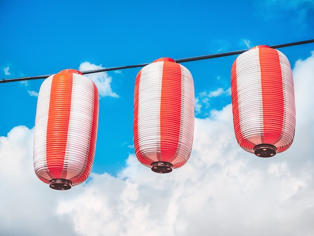 Papier rood-witte japanse lantaarns chochin opknoping op blauwe hemel