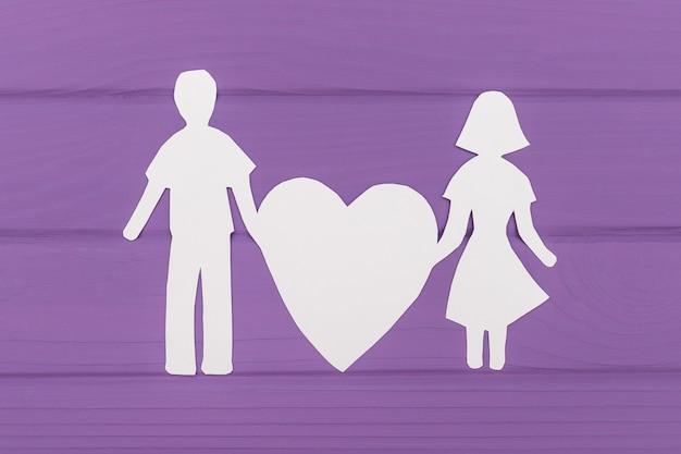 Papier silhouet van man en vrouw houdt groot hart