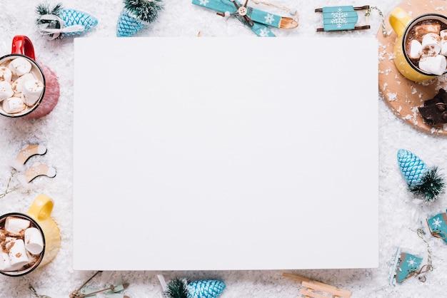 Papier tussen mokken met marshmallows en kerstmis speelgoed op sneeuw