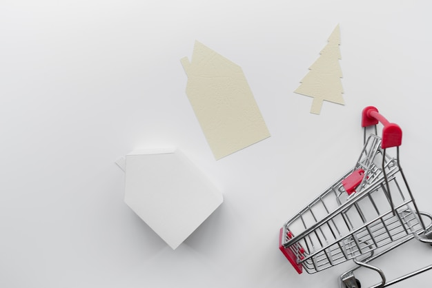 Papier uitgesneden huis en kerstboom met miniatuur huis model en winkelwagentje geïsoleerd op een witte achtergrond