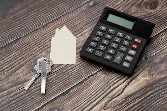 Papier uitgesneden huis met toetsen en rekenmachine op houten gestructureerde oppervlak