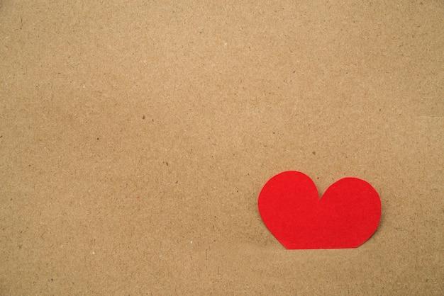 Papier uitgesneden rood hart vast in het karton