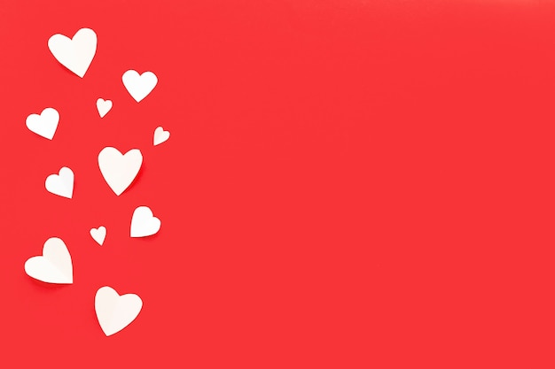 Papier valentijnsdag harten op rode achtergrond.