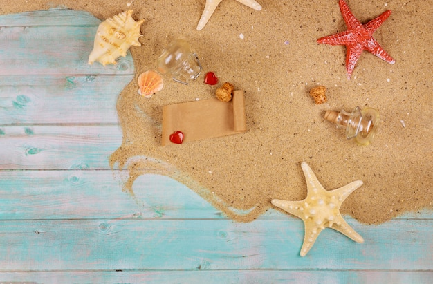 Papier van glazen fles op de oceaan kust met rode harten en zeester valentijnsdag dayor reizen concept