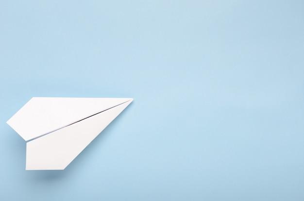 Papier vliegtuig op een blauwe achtergrond.