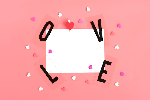 Papier voor het bericht, woord liefde van zwarte letters, snoep in de vorm van harten happy valentines day