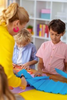 Papier voor jongens. jonge lerares met blond haar die roze oorbellen draagt en blauw papier snijdt voor jongens