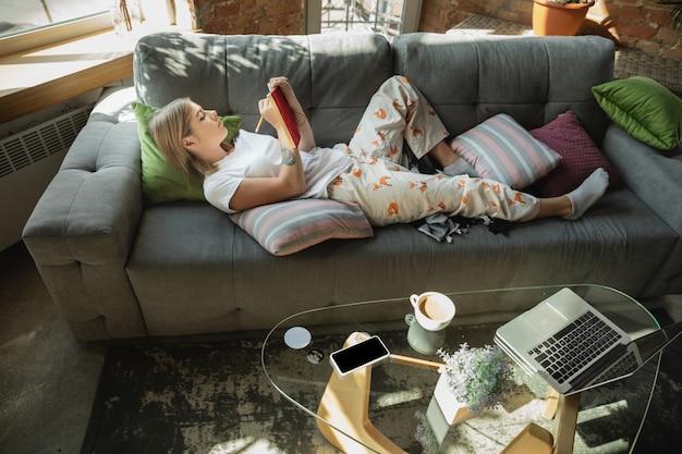 Papier werk. blanke vrouw, freelancer tijdens het werk in thuiskantoor tijdens quarantaine. jonge zakenvrouw thuis, zelf geïsoleerd. gadgets gebruiken. werken op afstand, preventie van verspreiding van coronavirus.