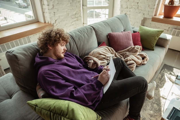 Papier werk. man aan het werk vanuit huis tijdens coronavirus of covid-19 quarantaine, extern kantoorconcept. jonge zakenman, manager die taken doet met smartphone, laptop, tablet heeft online conferentie.