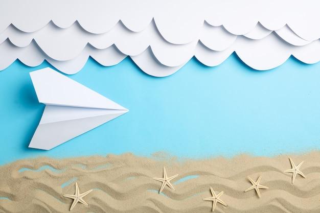 Papier wolken en vliegtuig, zand met zeesterren op blauw. vakantie