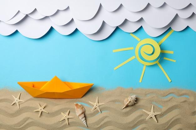 Papier wolken, zon en boot, zand met zeesterren op blauw. vakantie