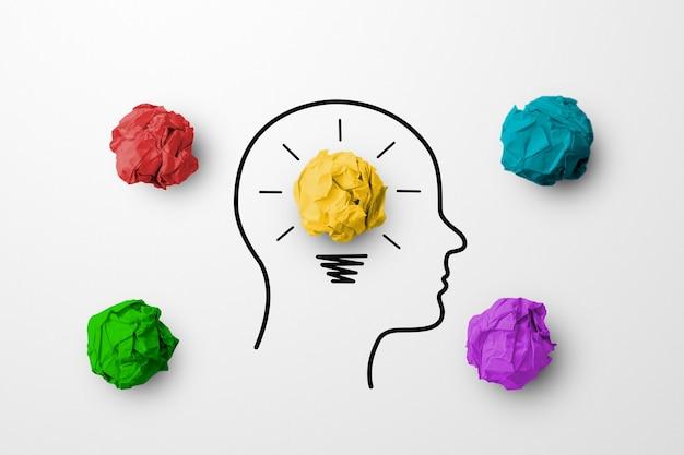 Papierafval bal gele kleur uitstekende andere groep met gloeilamp en hoofd menselijk symbool