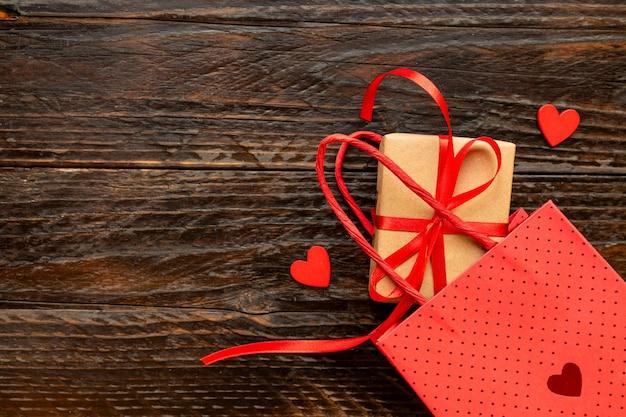 Papieren ambachtelijke geschenkdoos met rode strik, papieren zak en rode harten. feestelijk concept voor valentijnsdag, moederdag of verjaardag.