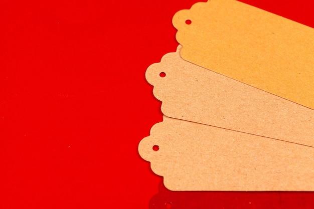 Papieren ambachtelijke tags op een rode achtergrond