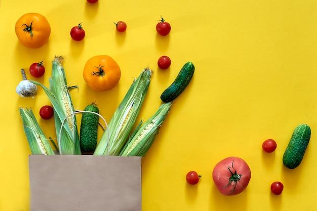 Papieren ambachtelijke tas met verschillende boodschappen op gele achtergrond. bovenaanzicht cherrytomaatjes, komkommers, knoflook. maïsoogstboerderijwinkel, levering van verse veganistische groene maaltijden.