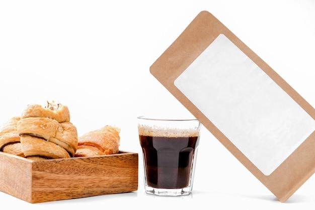 Papieren ambachtelijke verpakking met een wit blanco etiket, een glazen kopje zwarte koffie, een doos met croissants op wit