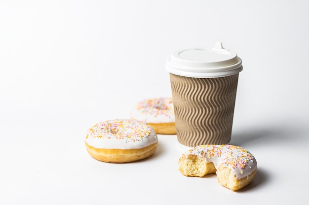 Papieren beker met een deksel, koffie of thee om te gaan en verse smakelijke donuts en zoete veelkleurige decoratieve snoepjes op een witte achtergrond. bakkerijconcept, vers gebak, heerlijk ontbijt, fast food.