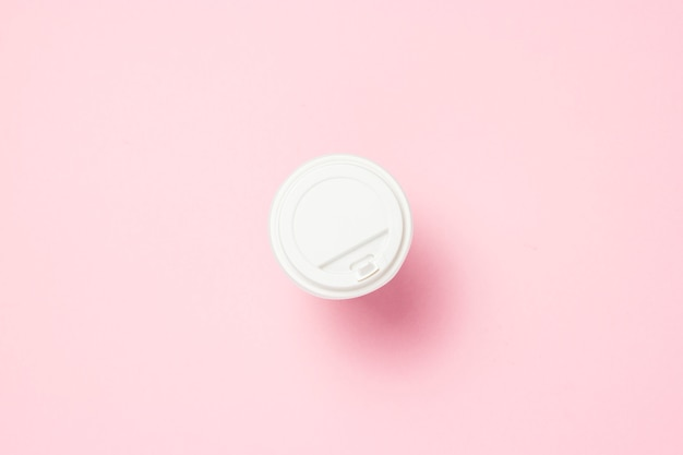Papieren beker met een plastic deksel, koffie of thee, op een roze achtergrond. fast-food concept, bakkerij, ontbijt, snoep, koffieshop, afhaalmaaltijden. kopie ruimte. plat lag, bovenaanzicht.