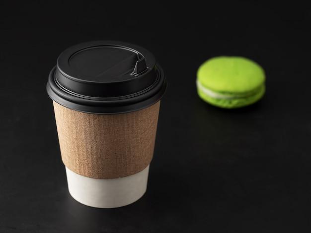 Papieren beker met een warm drankje, koffie of thee. in de buurt van bitterkoekjes. detailopname.