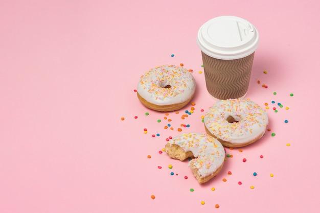 Papieren beker met koffie of thee, verse smakelijke zoete donuts op een roze achtergrond. fast-food concept, bakkerij, ontbijt, snoep, koffieshop. kopie ruimte.