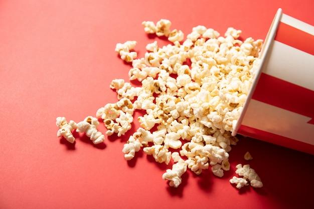 Papieren beker met popcorn op een rode achtergrond