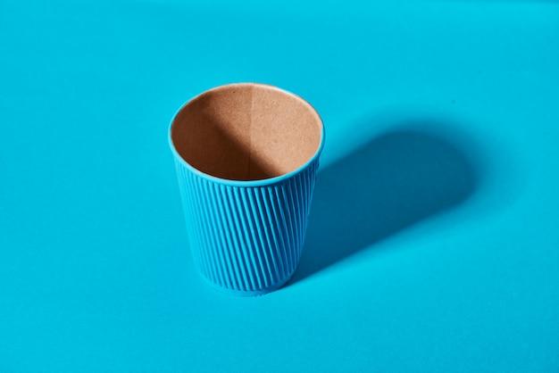 Papieren beker staat op effen gekleurd