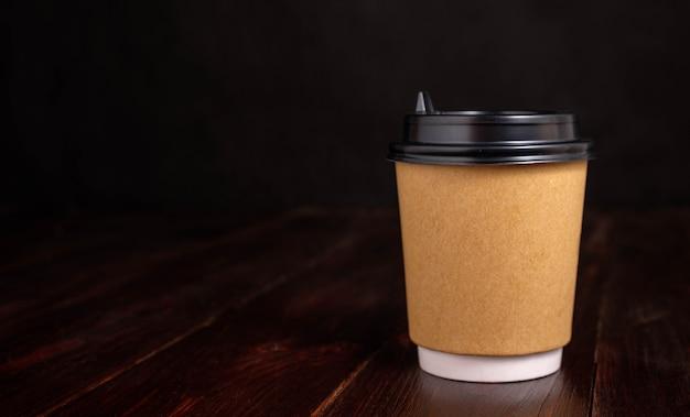 Papieren beker voor koffie op een houten donkere achtergrond