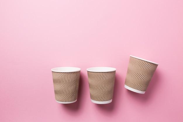 Papieren beker voor warme koffie of thee op een roze