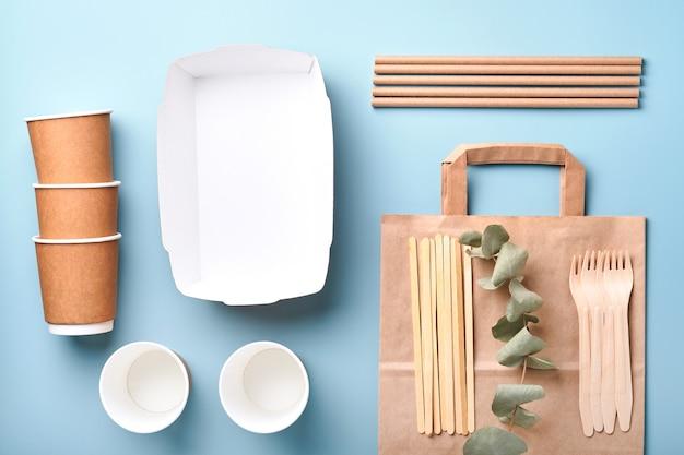 Papieren bekers, borden, tas, houten vorken, rietjes, fastfoodcontainers, houten bestek op lichtblauwe achtergrond. eco ambachtelijk papier servies. recycling- en voedselbezorgingsconcept. bespotten. bovenaanzicht