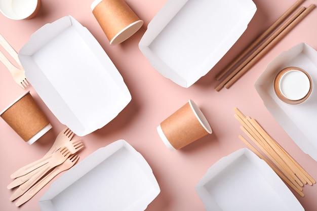 Papieren bekers, borden, tas, houten vorken, rietjes, fastfoodcontainers, houten bestek op roze achtergrond. eco ambachtelijk papier servies. recycling- en voedselbezorgingsconcept. bespotten. bovenaanzicht
