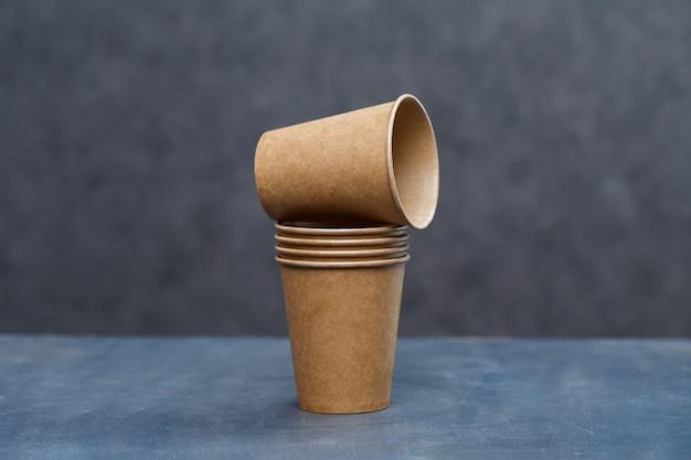 Papieren bekers om te drinken, gerechten. kartonnen wegwerpschalen gemaakt van milieuvriendelijke materialen. verstopt de natuur niet milieuvriendelijke, wegwerpbare, herbruikbare, composteerbare schalen.