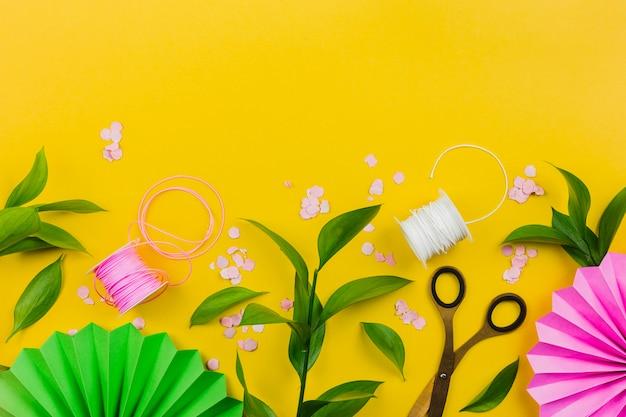 Papieren bloem; confetti; groene bladeren en draadspoel op gele achtergrond