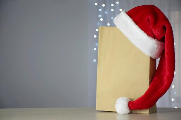 Papieren boodschappentas en kerstmuts met kerstverlichting