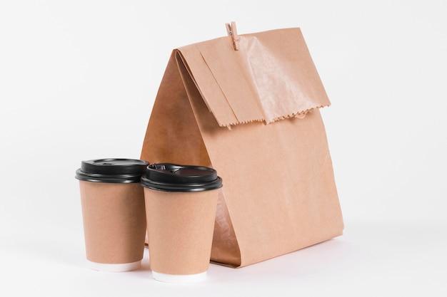 Papieren boodschappentas en koffie kopjes vooraanzicht