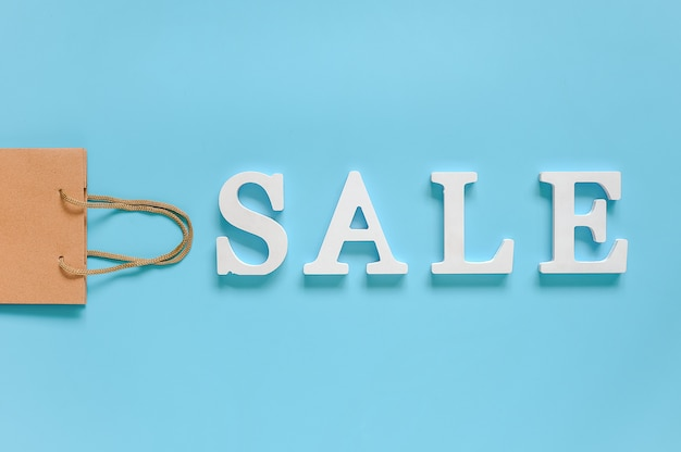 Papieren boodschappentas en tekst verkoop van witte volume letters op blauwe achtergrond