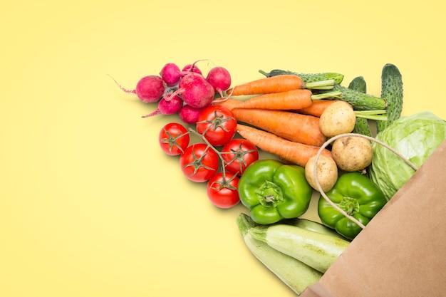 Papieren boodschappentas en verse biologische groenten op een lichtgele achtergrond. concept van het kopen van boerderij groenten, het verzorgen van gezondheid, vegetarisme. landelijke stijl, farm fair. plat lag, bovenaanzicht