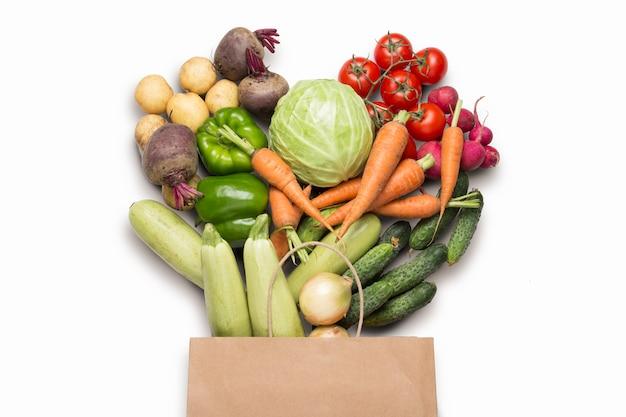 Papieren boodschappentas en verse biologische groenten op een witte ondergrond. concept van het kopen van boerderij groenten, het verzorgen van gezondheid, vegetarisme. landelijke stijl, farm fair. plat lag, bovenaanzicht