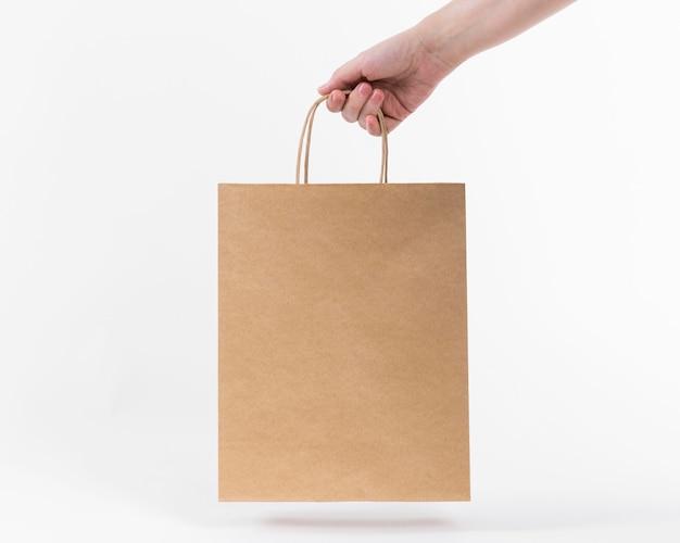 Papieren boodschappentas in de hand gehouden