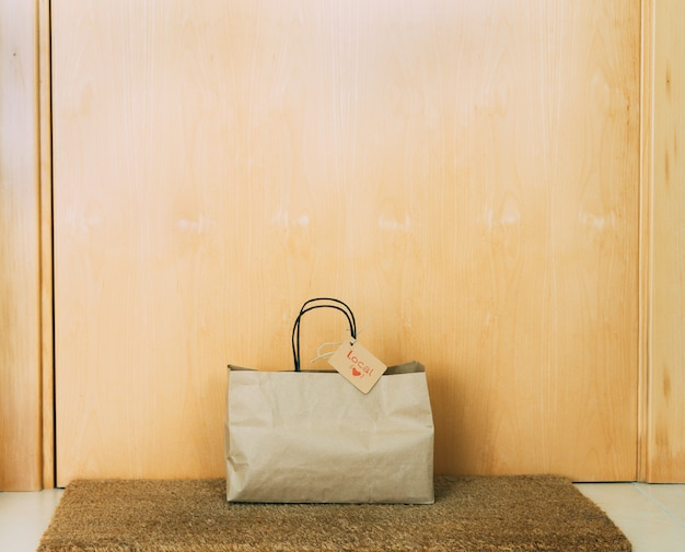 Papieren boodschappentas met kartonnen label op de voordeur van het huis. concept van winkelen.