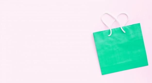 Papieren boodschappentas op roze achtergrond.