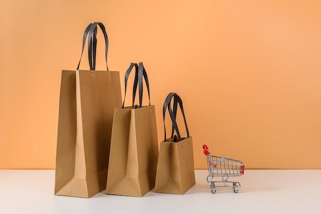 Papieren boodschappentassen en winkelwagen of trolley op witte tafel en pastel oranje muur