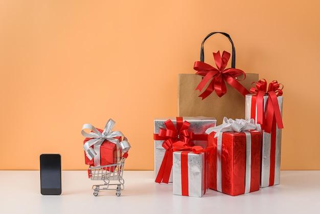 Papieren boodschappentassen en winkelwagen of trolley, veel gift box, telefoon op witte tafel en pastel