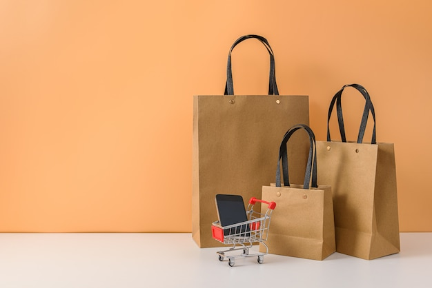 Papieren boodschappentassen en winkelwagentje of trolley met smartphone op witte tafel en pastel oranje achtergrond