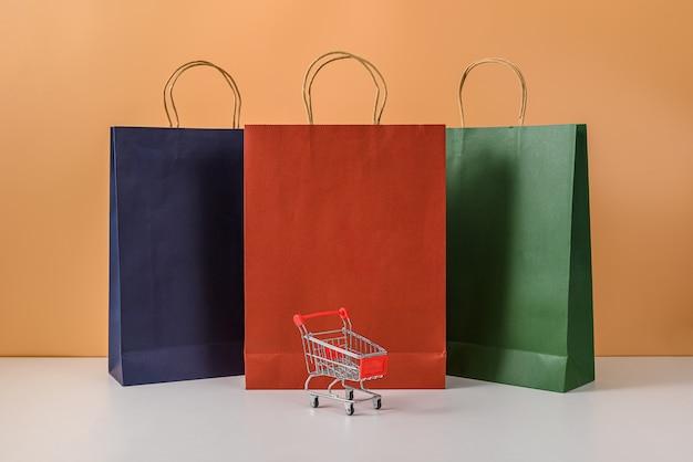 Papieren boodschappentassen en winkelwagentje of trolley met smartphone op witte tafel en pastel oranje muur